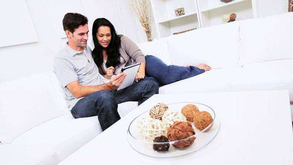 Young heterosexual Latin American couple relaxing home sofa wireless tablet Royalty-free stock video