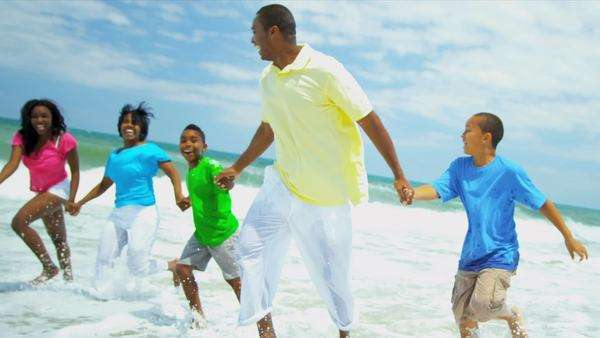 African American loving parents children holding hands enjoying running in ocean surfs on vacation shot on RED EPIC Royalty-free stock video
