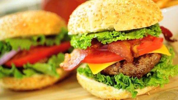 Appetizing classic bacon cheeseburger meal made from sesame seed bun filled with fresh salad vegetables and ground beef with bacon overcranking slow motion technique Royalty-free stock video