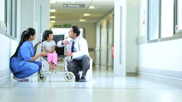 Asian Indian male pediatrician female nurse reassuring young ethnic child wheelchair hospital corridor Royalty-free stock video