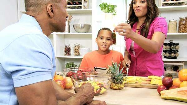 Healthy African American family home kitchen holding wireless tablet reading recipe for fresh fruit for healthy family living lifestyle Royalty-free stock video