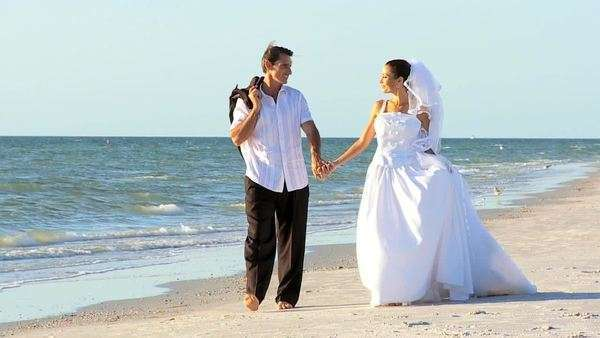 Bride & bridegroom walking barefoot on the beach after their wedding ceremony filmed at 60FPS Royalty-free stock video