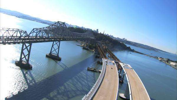 Aerial view flying over new bridge construction beside  Oakland Bay Bridge, San Francisco, USA Royalty-free stock video