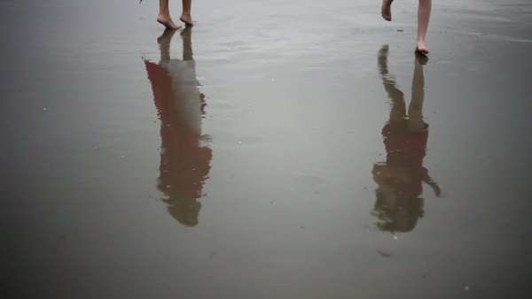 Reflection of mother and child in wet sand on beach Royalty-free stock video