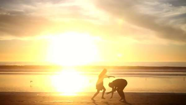 Sunrise on waterfront horizon as couple run and chase each other beach Royalty-free stock video