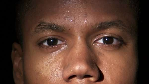 An extreme close up of a black man's sweaty face as he looks up at the camera. Royalty-free stock video