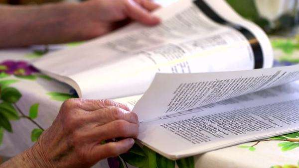 close-up hands of elderly woman thumbing through a magazine Royalty-free stock video