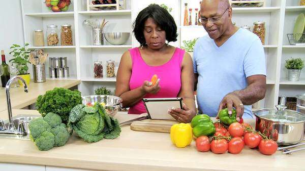 African American retired couple using wireless tablet technology home kitchen checking online healthy recipes using fresh vegetables slow motion Royalty-free stock video