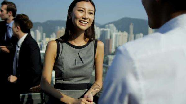 Head shoulders attractive young Asian Chinese businesswoman talking male associate rooftop modern city building colleagues shaking hands background shot on RED EPIC Royalty-free stock video