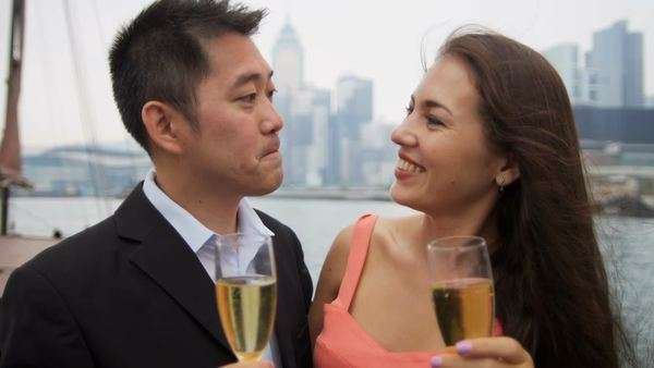 Close up Asian Western couple on corporate hospitality champagne trip on  traditionally designed Chinese junk Hong