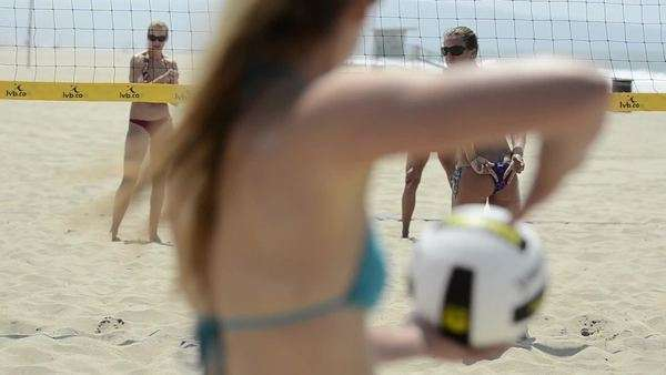 Close-up of women beach volleyball and a player signaling her partner who serves Royalty-free stock video