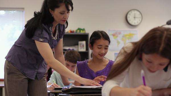 Teacher helping junior high student in classroom Royalty-free stock video