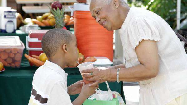 African American grandmother giving grandson orange juice Royalty-free stock video