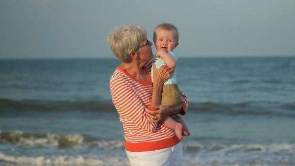 Caucasian grandmother holding baby on beach Royalty-free stock video