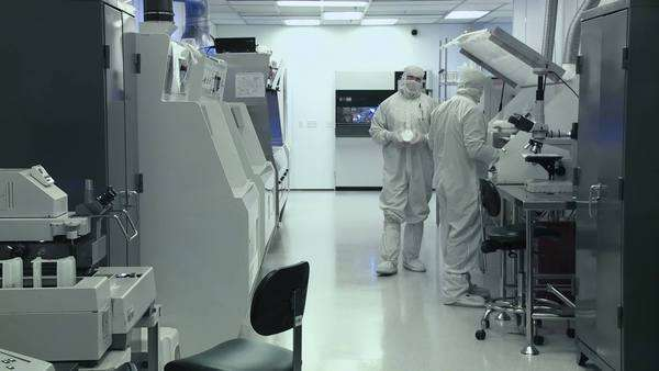 Scientists working on silicon chip manufacture in a clean room, wearing full body white coveralls to avoid contamination, extreme long shot Royalty-free stock video