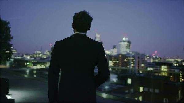 Successful businessman looks out at the view of the London city skyline at night Royalty-free stock video