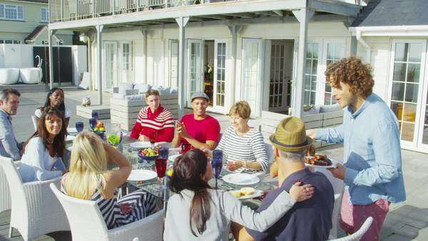 Happy group of family and friends enjoy a meal outdoors at luxury beachside home Royalty-free stock video
