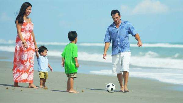 Latin American young loving parents walking on beach playing football with children shot on RED EPIC. Royalty-free stock video