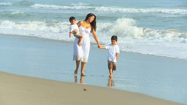 Young Latin American mother white sundress walking ocean shallows cute little boys Royalty-free stock video