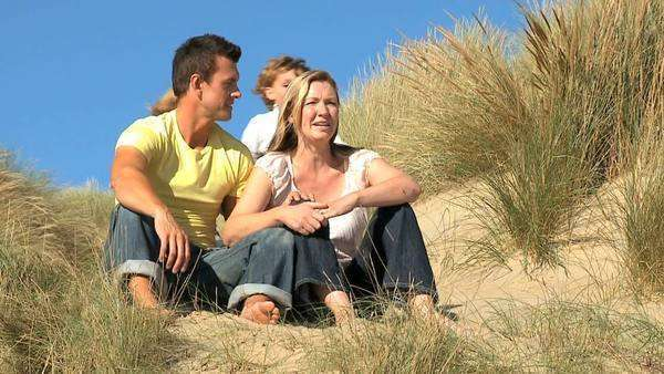 Attractive young Caucasian family enjoying leisure time together on coastal sand dunes filmed at 60fps. Royalty-free stock video