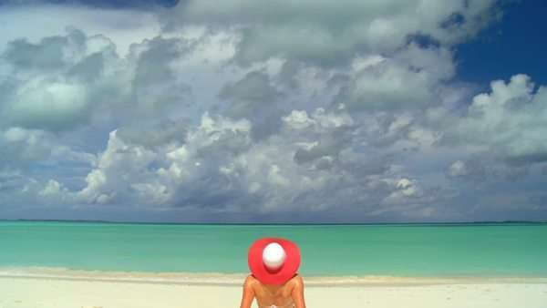 A woman in a straw hat observes an ocean horizon from a tropical beach. Royalty-free stock video