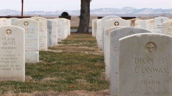 White marble headstones mark the graves of men and women buried in a military cemetery. Royalty-free stock video