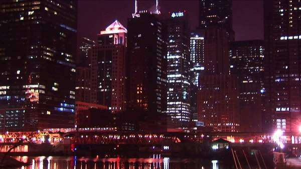 Chicago's buildings sparkle at night as a commuter train moves across the city. Royalty-free stock video
