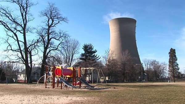 A children's colorful playground is seen in the foreground with a nuclear-power plant in the background. Royalty-free stock video