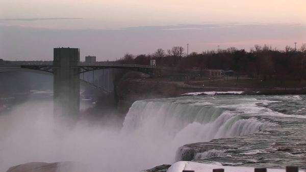 A moody view of Niagara Falls and bridge during golden-hour. Royalty-free stock video