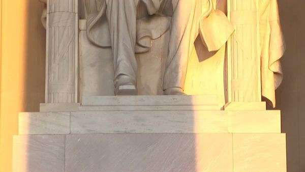 Golden light spills over a statue of President Abraham Lincoln. Royalty-free stock video