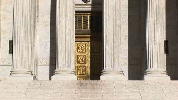 Sunlight reflects on the bright white pillars of the U.S. Supreme Court Building entrance. Royalty-free stock video