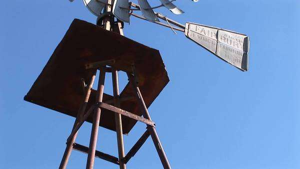 Pan-up from the base of a windmill to the blades turning in the wind. Royalty-free stock video