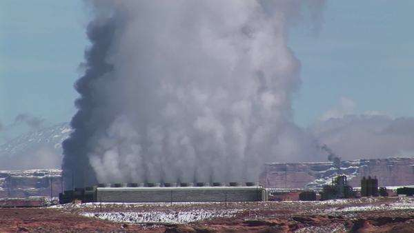 Medium-shot of a factory in the Arizona Desert emitting clouds of smoke. Royalty-free stock video