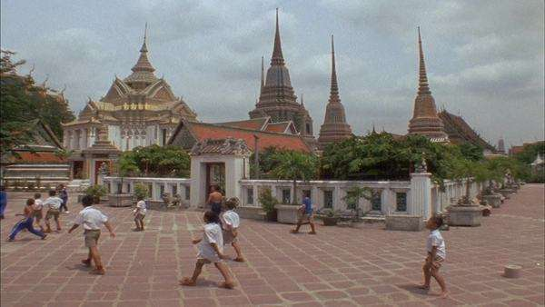 A medium shot of children playing soccer in the courtyard of a Buddhist temple and school. Royalty-free stock video