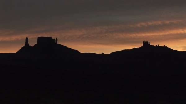 A horizon of desert buttes and rock formations is silhouetted during the golden-hour. Royalty-free stock video