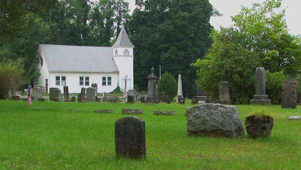 Gravestones stand in an old New England graveyard near a white church. Royalty-free stock video