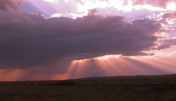 Beautiful sun beams burst forth from dark clouds onto open plains. Royalty-free stock video