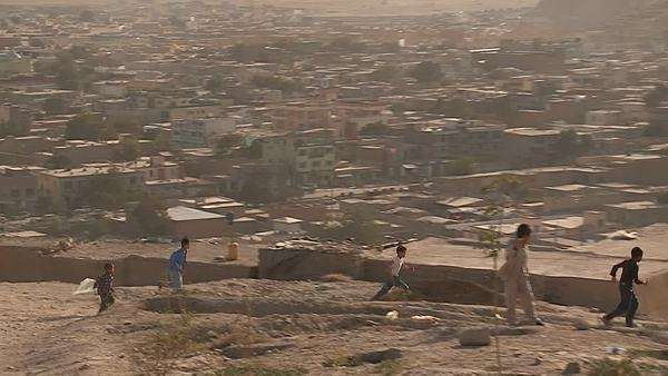 Boys play on the hillsides flying kites in modern Kabul, Afghanistan. Royalty-free stock video