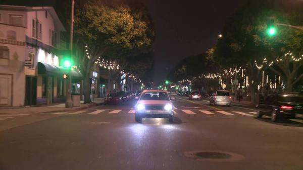 A vehicle drives through a city's downtown, which is decorated with strings of white lights. Royalty-free stock video