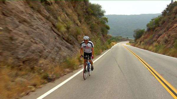 A bicyclist peddles along a highway in a mountainous area. Royalty-free stock video