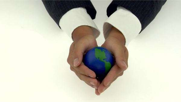 A pair of cupped hands holds a small globe. Royalty-free stock video