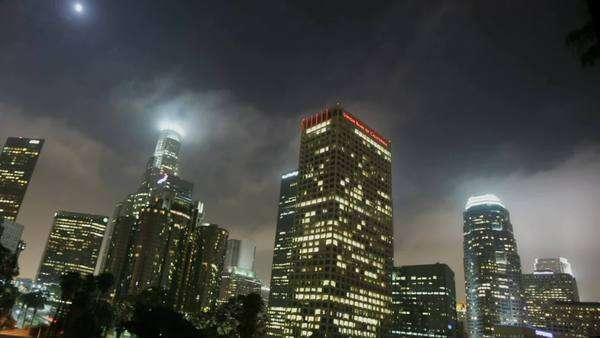 Lights illuminate high rise buildings in a downtown area at night. Royalty-free stock video