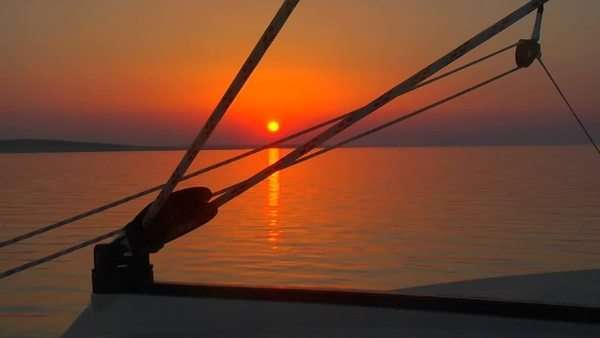 A beautiful sunset seen through the rigging of a sailboat. Royalty-free stock video