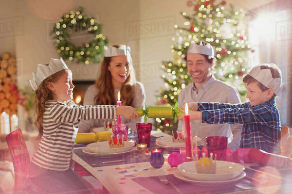 Family in paper crowns pulling Christmas cracker at dining table Royalty-free stock photo