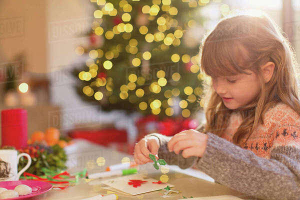 Girl making Christmas decorations at table Royalty-free stock photo