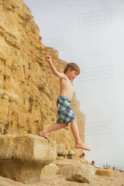 Boy in swim trunks jumping on beach rock Royalty-free stock photo
