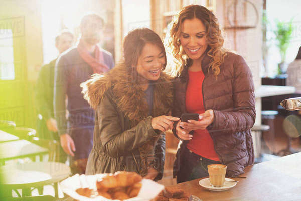 Women friends using cell phone in cafe Royalty-free stock photo