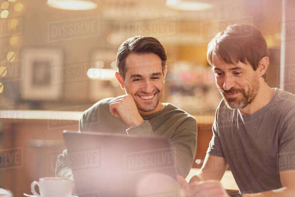 Men friends using laptop and drinking coffee in cafe Royalty-free stock photo
