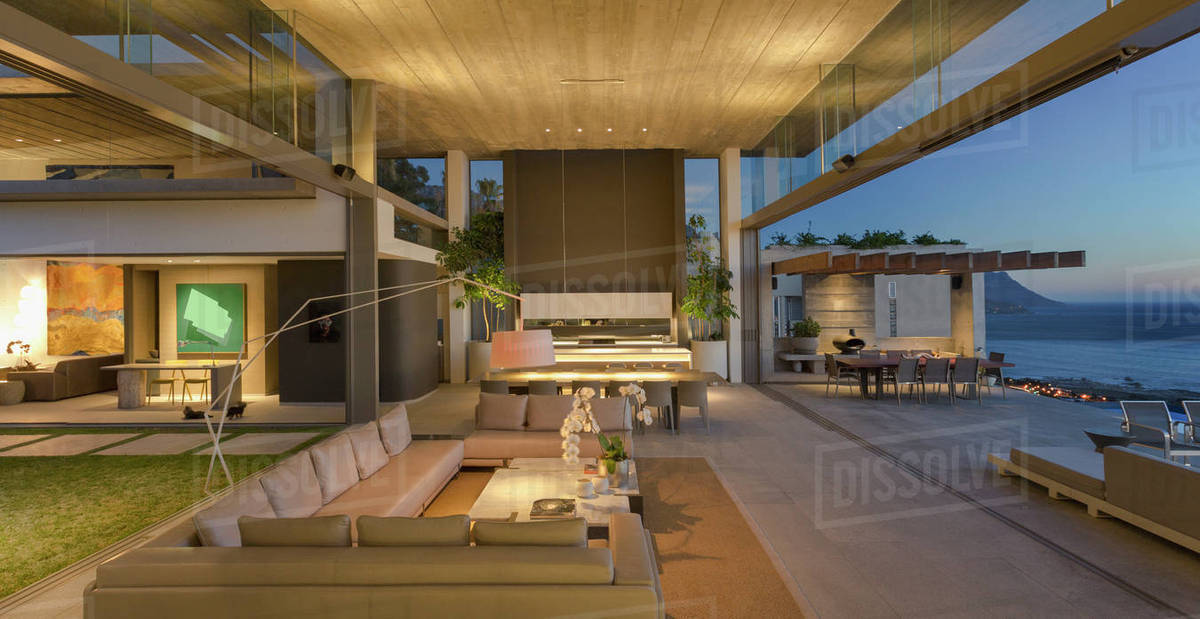 Illuminated Modern Luxury Home Showcase Interior Living Room Open To Patio At Dusk Stock Photo