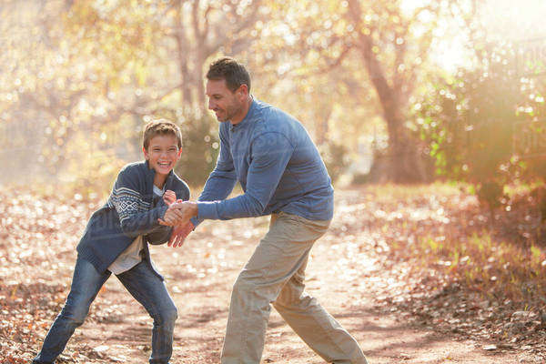 Playful father and son on path in woods Royalty-free stock photo